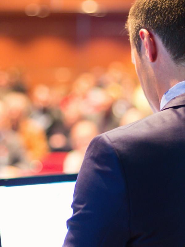 orateur public congrès costume noir et chemise bleue